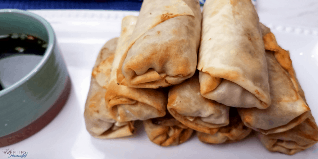 delicious egg rolls nicely stacked with a side of sauce